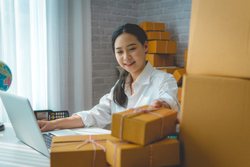 Small business owner, woman checking purchase order in mobile phone and write in the delivery on package box working at home office. online marketing is startup SME entrepreneur and freelance concept.
