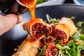 Pouring chilli sauce onto spring rolls