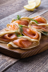 Smoked salmon appetizer, stuffed crepes on wooden board
