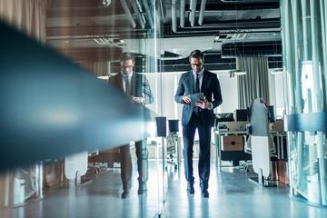 Obraz Businessman walking through company and using tablet. - fototapety do salonu