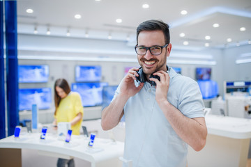 Happy man posing with earphones in tech store. Technology shopping concept.