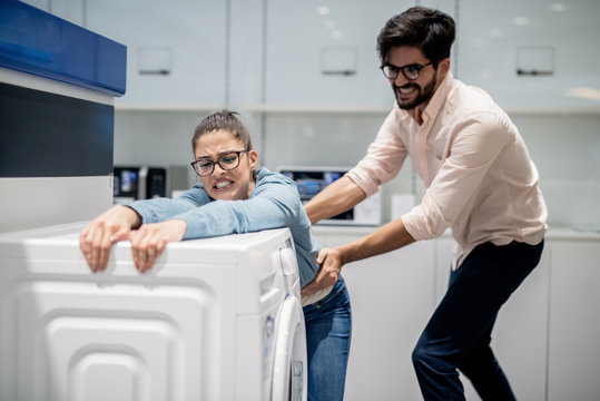 Man taking away wife from washing machine. Whiteware department interior.