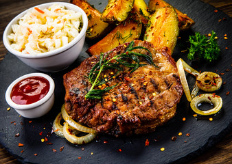 Grilled steak with baked potatoes and vegetables served on black stone plate on wooden table
