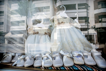 Dresses and shoes to make first communion reflected in showcase, conceptual image