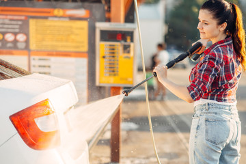Cute woman with car washer on self service carwash
