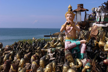 A piper figure sits atop a collection of statues at a shrine overlooking the ocean in Thailand.