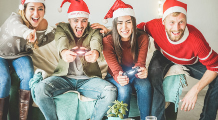 Group of happy friends having fun with video games console on christmas time