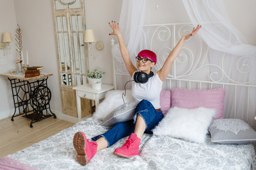 positive girl with short pink hair listening to music on the bed in shoes