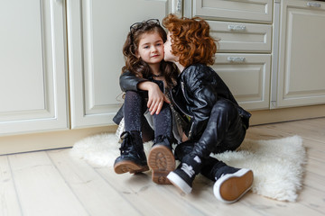 redhead little boy kissing a little girl at home on the floor