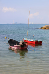 Two small traditional wooden Asian fishing boats moored in a calm bay