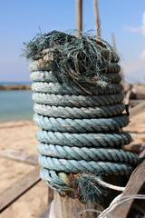 A thick frayed blue rope is wound around a wooden pole at a small fishing pier with beach, ocean and blue sky visible in the background