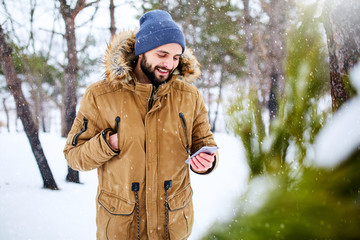 Smiling bearded man wears warm winter clothes and using smartphone with fast internet connection in country side. Handsome man texting with cellphone and using apps in forest. Snowfall in woods.