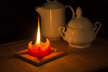 Red candle illuminates a jug and a cup.