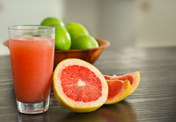 Glass of freshly squeezed grapefruit juice with grapefruit slices.
