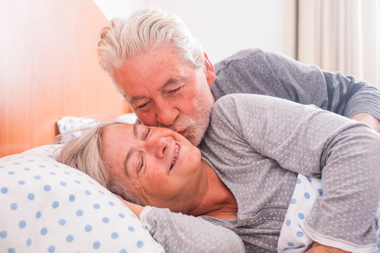 Couple of senior man and woman waking up and smiling with a hug while are in the bed at home. He kiss her with love for a life together