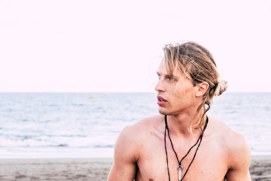 nice beautiful young man portrait at the beach with ocean in background - attracive male caucasian people wild style and nature feeling - travel concept