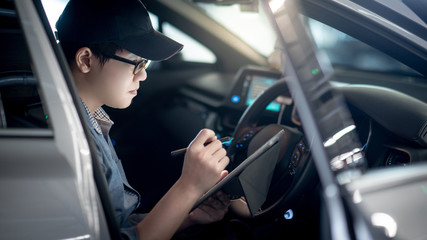 Asian auto mechanic sitting on driver seat checking the car using digital tablet in auto service garage. Mechanical maintenance engineer working in automotive industry. Automobile servicing and repair