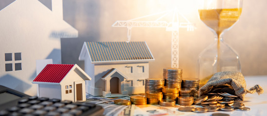 Real estate or property development. Construction business investment concept. Home mortgage loan rate. Coin stack on international banknotes with calculator, house and crane models on the table.