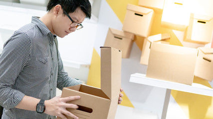 Young Asian man opening cardboard box package. Packaging design product for shopping lifestyle concept