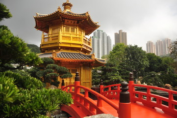 Beautiful oriental garden in city, View of golden oriental tower with red bridge in green Nan Lian garden with cityscape on background, Hong Kong