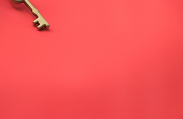 Image of golden key is on a top corner on a beautiful red background. Let dreams come true. Concept: Real estate deal.
