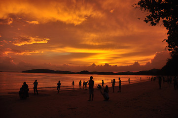 People on sandy shore in sunset, Silhouettes of people spending time on tropical coastline with golden bright sky in sunset light, Thailand.