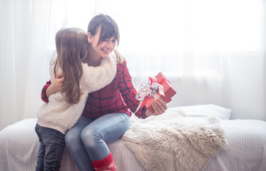 Christmas concept, the Daughter gives a gift to her mother