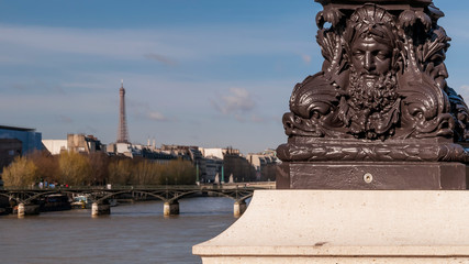 Detail of a street lamp on the Seine in Paris, France, with the Eiffel Tower in the background