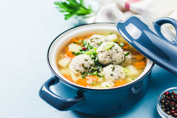 Meatball vegetable soup in a pot on light blue background. Selective focus, space for text.