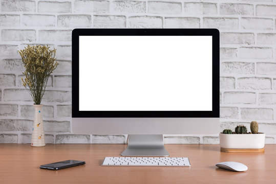 Blank screen of all in one computer with dry flowers, iPhone X and cactus vase on white bricks background