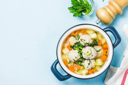 Meatball vegetable soup in a pot on light blue background. Top view, space for text.