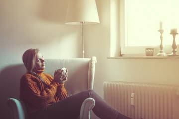Junge Frau schaut aus dem Fenster und trinkt eine Tasse Tee