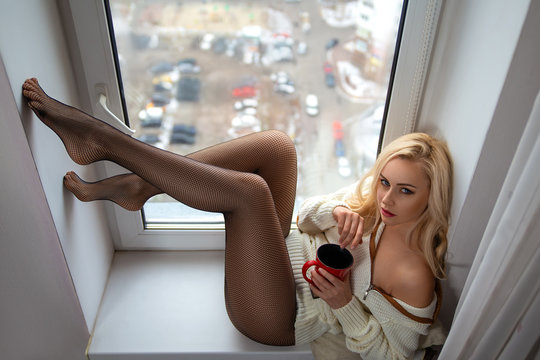Girl with perfect legs in pantyhose posing on the windowsill