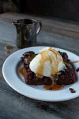 Caramel drizzled brownies with vanilla bean ice cream scoop on white plate