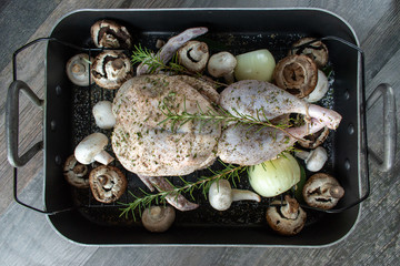 Raw duck with rosemary and onions with potatoes and mushrooms on baking rack flat lay