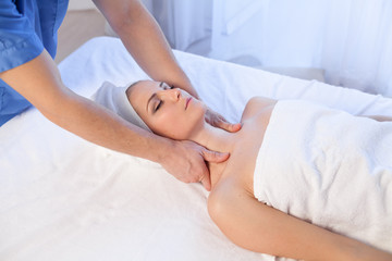 a massage therapist makes a woman face and neck massage in the Spa