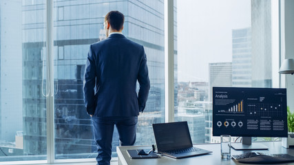 Confident Businessman in a Suit Contemplating Business Deal in His Office, Looking out of the Window. Window Has Panoramic View on Big City Business District. Wall mural