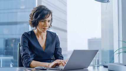 Confident Businesswoman Sitting at Her Desk and Working on a Laptop in Her Modern Office. Stylish Beautiful Woman Doing Important Job. In the Window Big City Business District View.  Wall mural