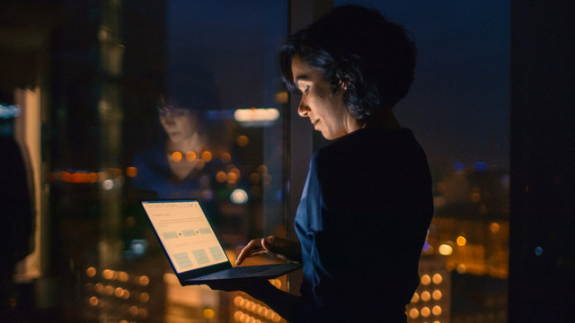Successful, Stylishly Dressed Businesswoman Holds Laptop While Standing Near the Window of Her Office. Late at Night Professional Woman Doing Important Job. Window Has Big City View with Many Lights.
