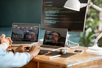 Programmers writing a program code sitting at the workplace with three monitors in the office. Cropped imaage with no face