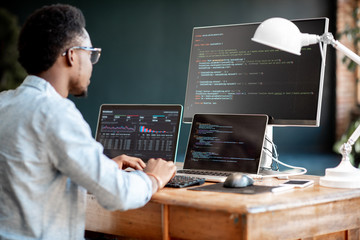 Young african male programmer writing program code sitting at the workplace with three monitors in the office. Image focused on the screen - fototapety na wymiar