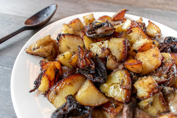 Side dish of roasted vegetables of carrots, potatoes, onions, and mushrooms