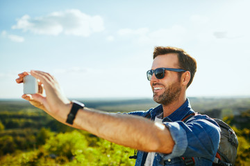 Cheerful man taking selfie while hiking in the mountains on sunny day