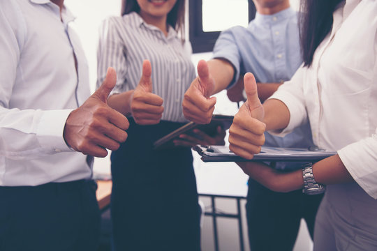 Team businessman shows thumb to appreciate each other.