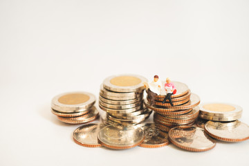 Miniature people man and woman sitting on stack coins isolate on white background using as business and finance concept