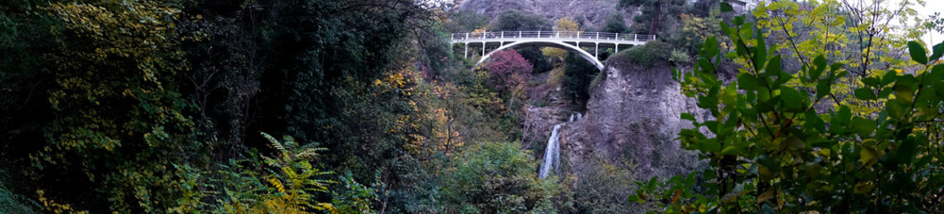 Panoramic photo of a waterfall in autumn park