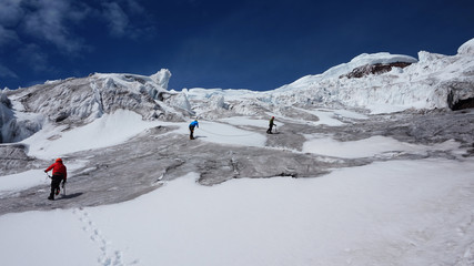 Group of climbers climbing towards the summit of Cotopaxi volcano during a sunny day