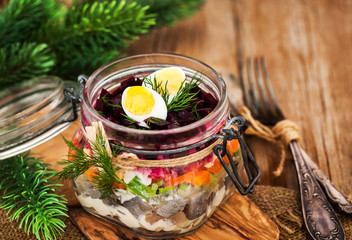 Traditional Russian layered betroot and herring salad (under a fur coat) in glass jar