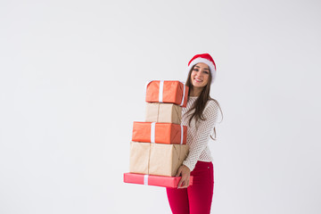 Christmas, holidays and presents concept - woman in santa hat holding a lot of gifts on white background with copy space