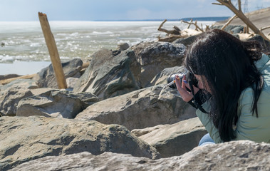 A girl in a warm jacket with a camera and a cigarette on the rocky shore of an ice-covered pond, Smoking, taking pictures of the landscape.